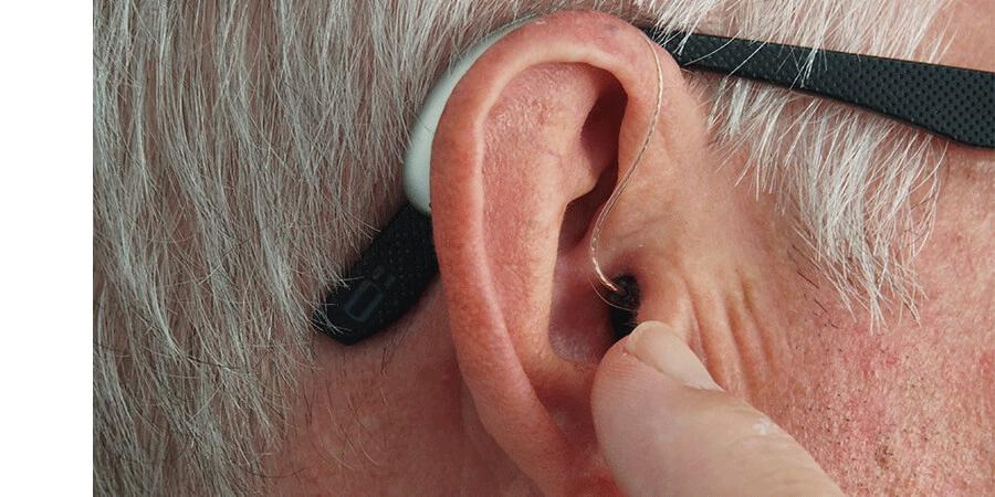 Ohr eines Brillenträgers mit Hörgerät